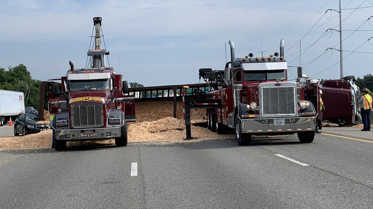 1 injured, driver charged in crash that led to overturned tractor-trailer