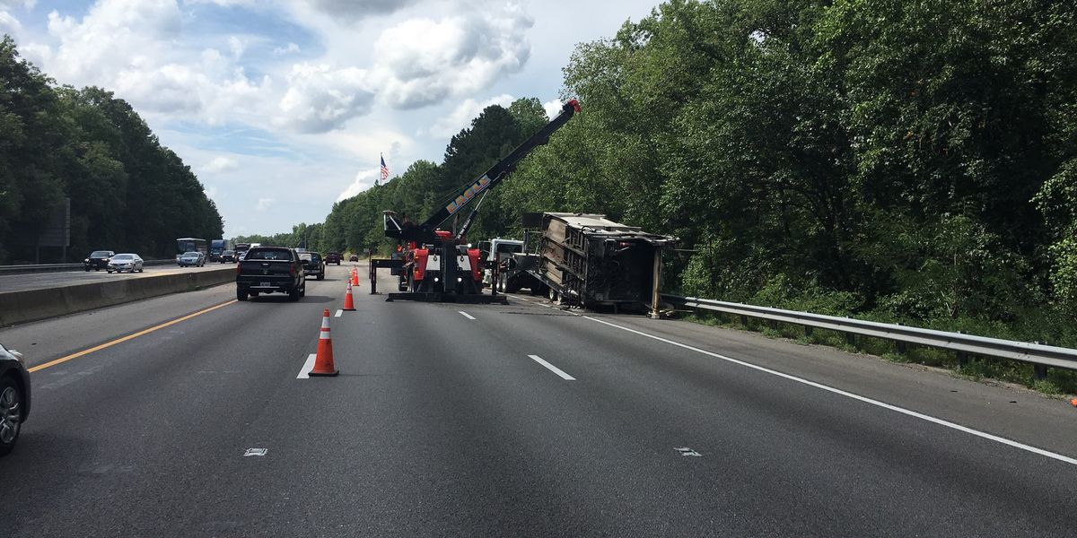 Driver injured when trash truck blows tire, trailer overturns on I-95