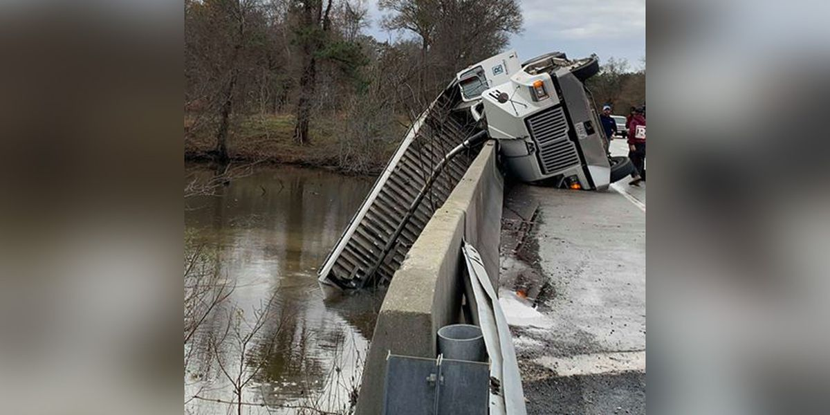 Driver charged after dump truck crashes, hangs off bridge