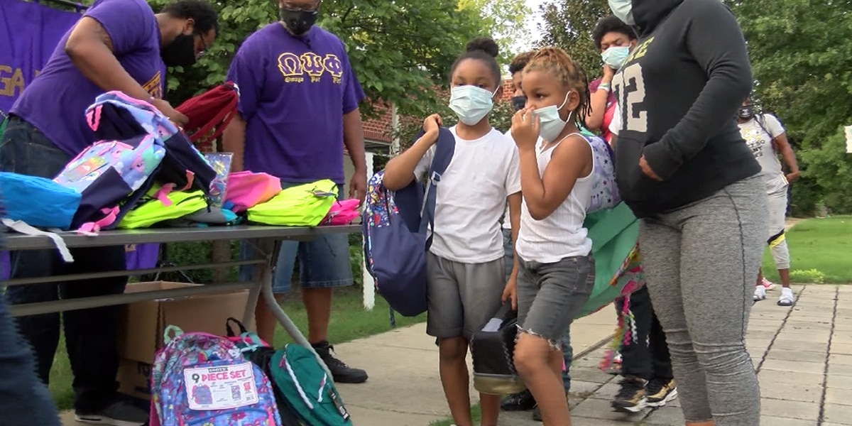 Brothers of Omega Psi Phi hand out backpacks, school supplies
